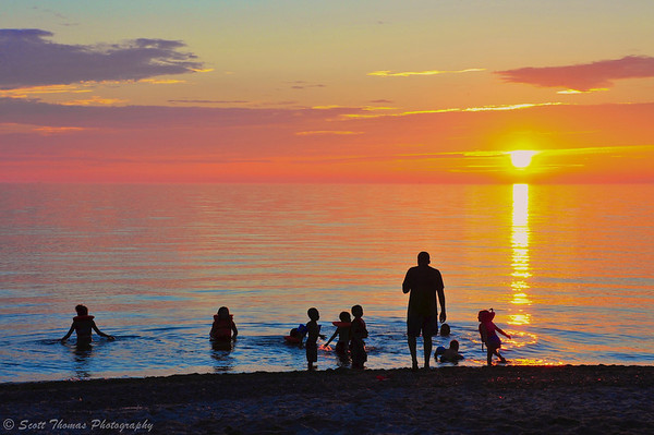 A group of swimmers enjoying Lake Ontario waters as the Sun sets at Brennan's Beach RV Campground and Resort near Pulaski, New York.