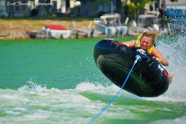 A girl holds on tight as her tube being pulled by a power boat goes airborne over a wave on Lake Ontario.