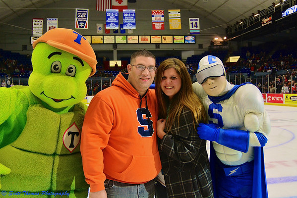 Newly engaged couple posing with mascots at a Syracuse Crunch game in the Onondaga County War Memorial on Saturday, December 14, 2013.