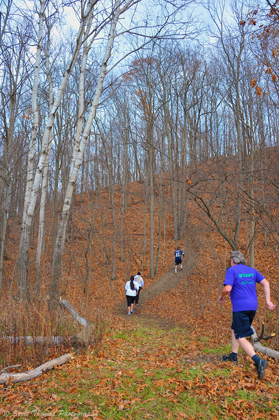 5K event runners climbing a hill during the Onondaga Nation Trail Run near Syracuse, New York.