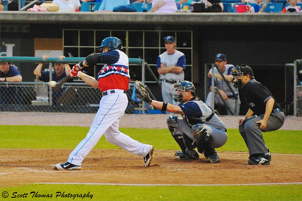 Getting the object of the sport in the photo is very important like the baseball the batter is hitting here.