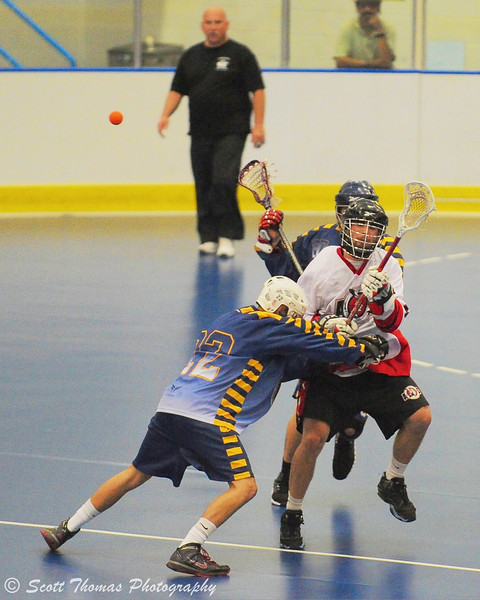 Allegany Arrows try to stop an Onondaga Red Hawk from clearing the ball in hard hitting action of box lacrosse.
