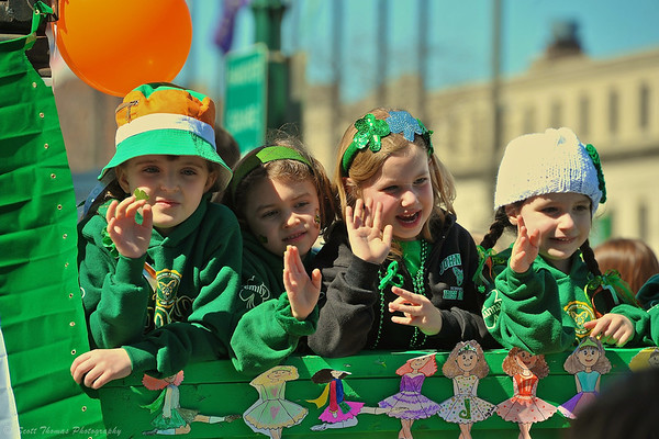 Girls waving to the crowd from a float in the Syracuse St. Patrick's Day Parade in Syracuse, New York.