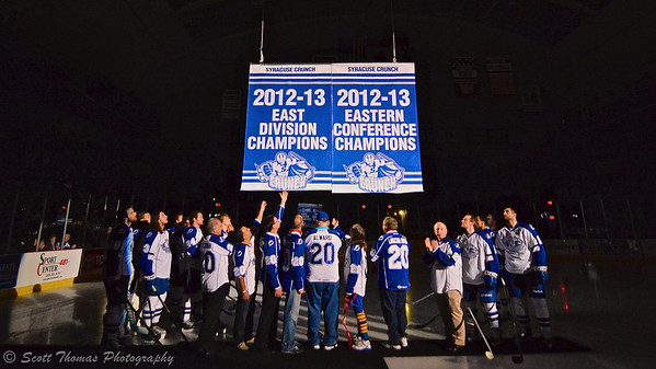 To kick off the Syracuse Crunch's 20th season, 20 year season ticket holders, 20 year sponsors and members from last year's team raise the Eastern Division and Conference Championship banners before playing the Rochester Americans in an American Hockey League (AHL) game at the Onondaga County War Memorial on Saturday, October 12, 2013.