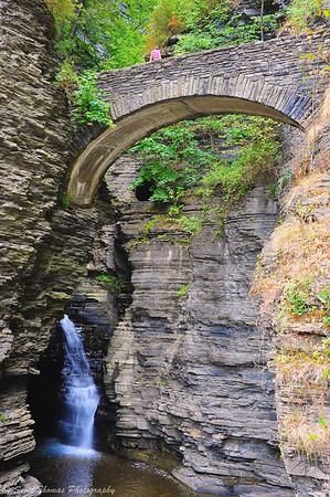 A tourist takes a break on one of several stone bridges along the Gorge Trail in Watkins Glen State Park, Watkins Glen, New York.