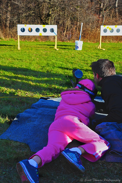 Father helping his daughter with a paintball rifle during the Onondaga Parks Open House at Highland Forest in Fabius, New York.