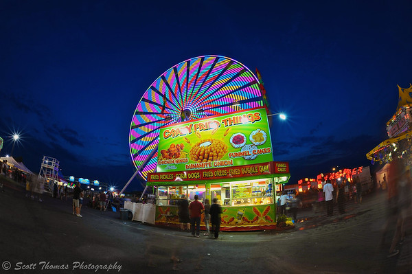 The Big Wheel looms over the Crazy Fried Things food stand on the Midway of The Great New York State Fair in Syracuse, New York.