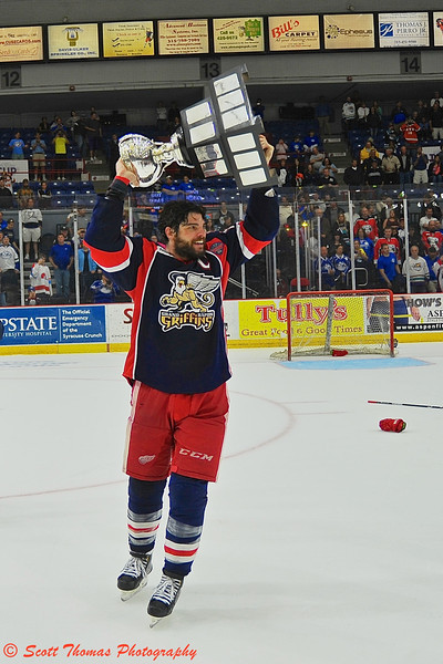 Grand Rapids Griffins Captain Jeff Hoggan (10) was the first to parade with the Calder Cup on the ice at the Onondaga County War Memorial in Syracuse, New York on Tuesday, June 18, 2013 after his team defeated the Syracuse Crunch in a Best-of-7 game series, 4 to 2.