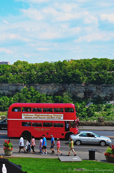The Deluxe Sightseeing Tours Red Double Decker bus full of tourists drives past the Niagara River gorge and falls at Niagara Falls in Ontario, Canada.