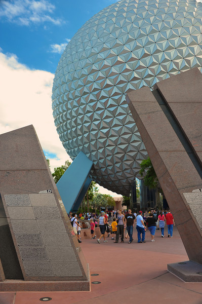 Tourists are framed between Leave A Legacy structures near Spaceship Earth.