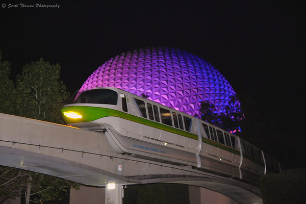 Monorail Green passing Spaceship Earth at night.