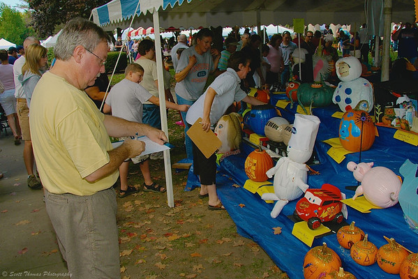 A judge looking over entries for a youth pumpkin decorating contest at the Great Cortland Pumpkinfest in Cortland, New York.