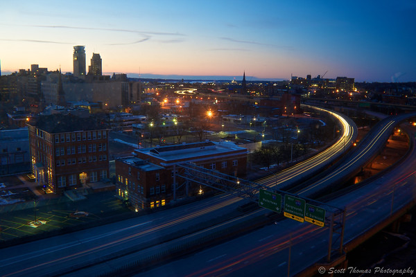 Cars streak pass as blue hour starts to descend over Syracuse, New York on a cold winter's evening.