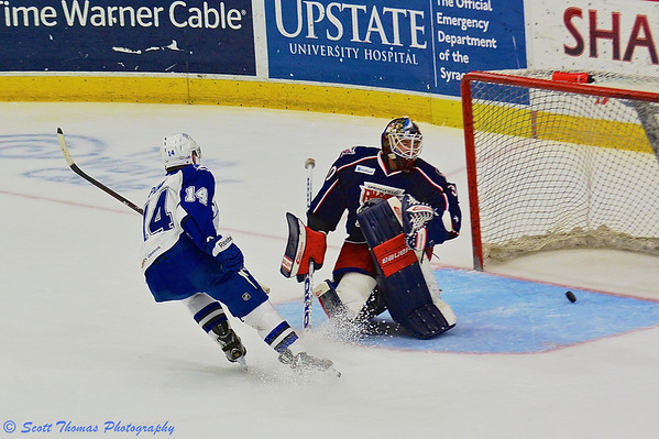 Syracuse Crunch Richard Panik (14) beats Springfield Falcons goalie Curtis McElhinney (30) for the Syracuse Crunch's first goal in American Hockey League (AHL) Calder Cup Playoff action at the Onondaga County War Memorial on Wednesday, May 15, 2013.