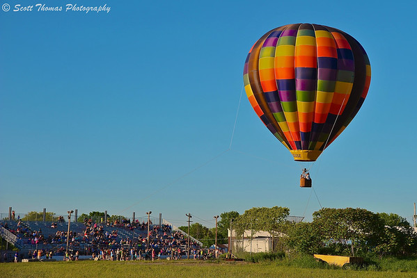 A tethered hot air balloon gives spectators rides during the Oswego Balloonfest at the Oswego Country Fairgrounds in Sandy Creek, New York.