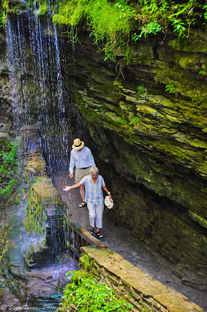 A woman reaches out to feel the water falling from an overhang along the Gorge Trail in Watkins Glen State Park, Watkins Glen, New York.