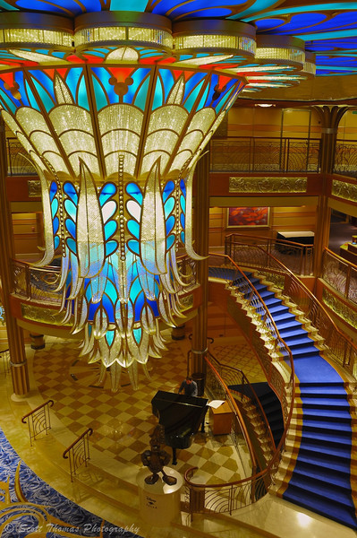 The crystal chandelier in the Disney Dream's atrium hangs over the grand staircase, piano and Admiral Donald Duck's statue.