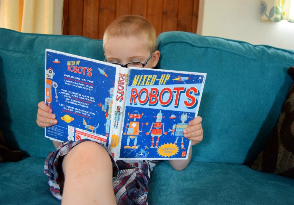 Little man looking at mixed up robots book