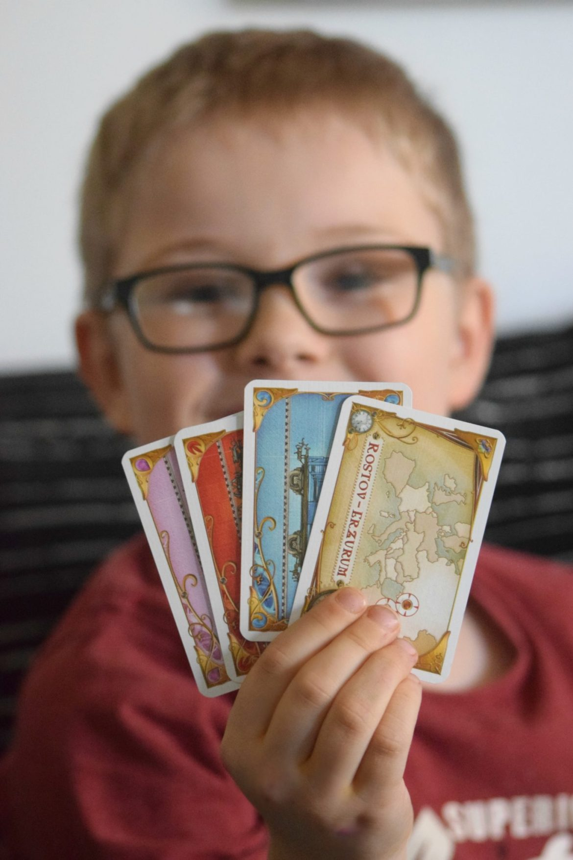 My son holding the playing cards for Ticket to ride Europe board game.