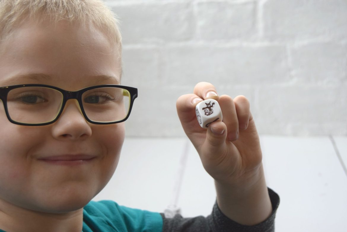 Rory's Story Cubes game. My son holding one of the 9 story dice used to make a story.