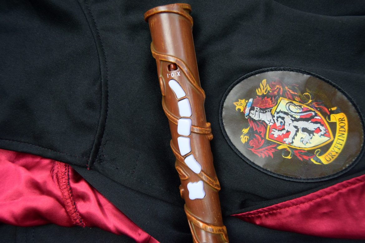 Harry potter toy wand with Gryffindor gown.