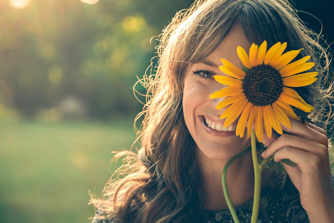 A lady smiling and holding up a sunflower.