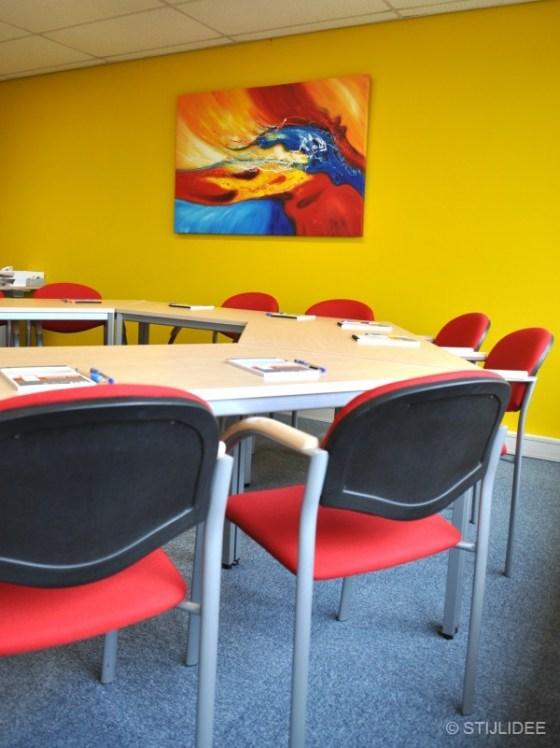 gele vergaderkamer met rode stoelen en kunst in Capelle na STIJLIDEE Kleuradvies, Interieuradvies en Styling