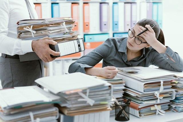 Sekretärin mit vollem Schreibtisch