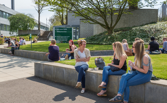 Students sitting on the wall outside a lecture theatre