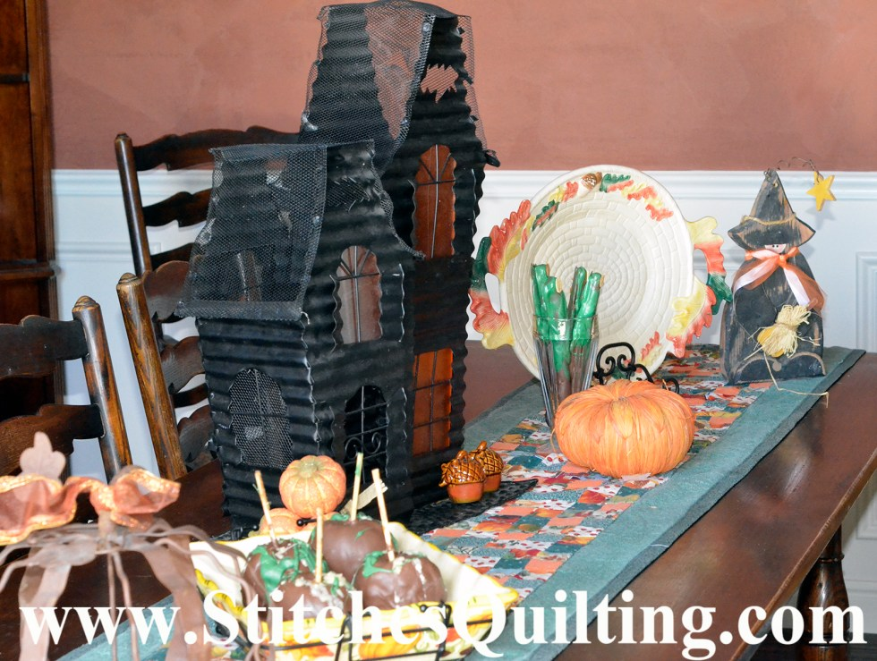 This is our dining table room table decorated! The table runner is simple, just small scraps of fabric squares stitched together and bordered. Halloween decorations are out for such a short time of year so why make something too complicated?