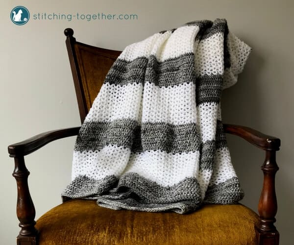 A beautiful crochet throw which will compliment any home decor. Easy stitches, repeated in large stripes gives the blanket texture and variety but keeps the pattern simple and enjoyable. Don't forget to save this free crochet pattern for the Coco Crochet throw. | Crochet Blanket, Crochet Throw, gray and white striped throw #stitchingtog