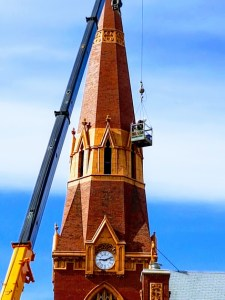 St. John's Cathedral Steeple inspected by masons using crane