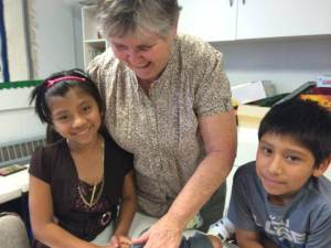 A sister working with two smiling latino youth, a boy and a girl