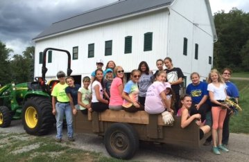 A group of Earth Tones volunteers on the back of a truck and standing behind it, smiling