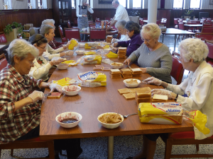 Sisters and Associates prepare peanut butter and jelly sandwiches for the Salvation Army.