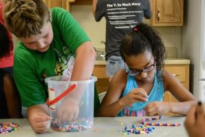One child scoops beads out of a bucket while another carefully strings beads onto a necklace.