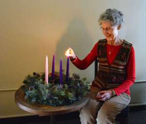 Associate Linda Biel lighting the first Advent candle.