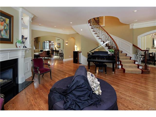 Entry hall/Gathering room with panel and crown molding show off the custom curved iron and wood staircase