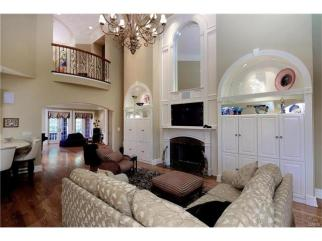 Double height ceiling with extensive crown, large framed mirror above fireplace with granite surround, built-in arched display case and cabinets, beautiful chandelier with lift