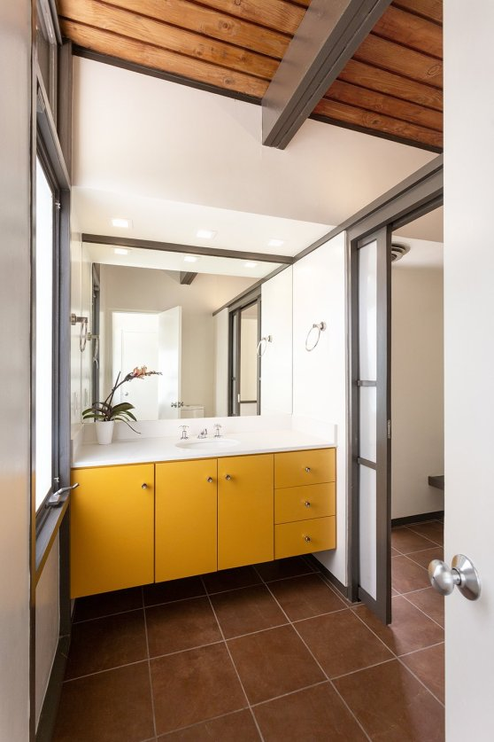 a-look-at-one-of-the-two-secondary-bathrooms-this-one-with-a-brightly-painted-vanity-a-screen-door-provides-privacy-for-a-shower-and-changing-area