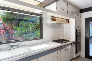 the-kitchen-features-original-cabinetry-with-a-large-window-above-the-sink-providing-natural-light-the-space-was-updated-with-new-appliances-and-fixtures