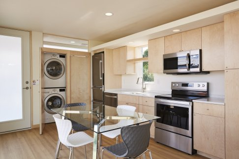 the-kitchen-cabinetry-and-the-flooring-throughout-the-tiny-home-are-finished-with-maple-a-clothes-washer-and-dryer-are-situated-behind-maple-doors-at-one-end-of-the-kitchen-and-dining-area