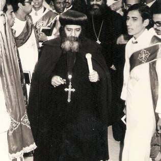 Welcoming Pope Shenouda III during his visit to attend the 100 years anniversary of Virgin Mary Church in Elsagha, Tanta, Egypt - 1975. In the picture, the Late Bishop Youannes of Gharbia and Father Metias (a deacon in that time) holding the Service of the Deacons Book.