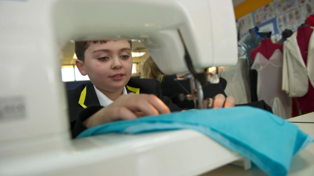 Boy using sewing machine