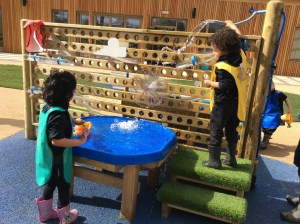 Nursery pupils playing at the water station