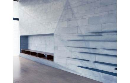 Long horizontal shelf-like surfaces run across the wall separated optically by color-coordinated lines.