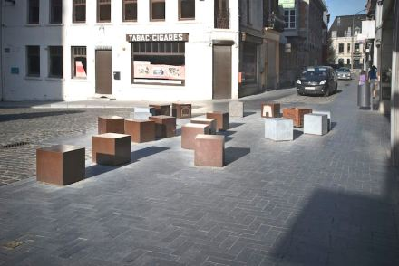 Corten-Steel cubes serve as seating. The symbols engraved in the surface provide information on the city's history.