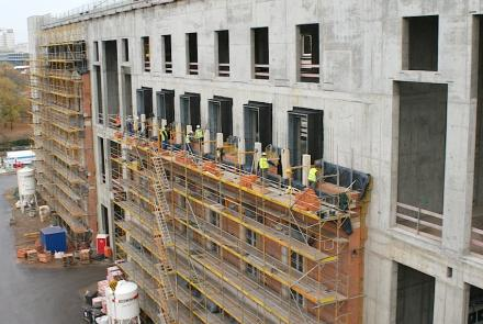Per poter reggere il carico dei pesanti elementi in pietra arenaria si mette una parete di spessore di 60 cm di mattoni davanti al muro in cemento armato.