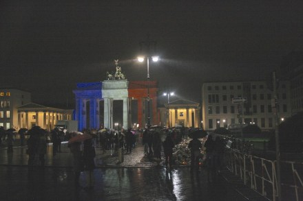 The Brandenburg Gate in Berlin in the colors of the French nation. At the right, flowers and candles in front of the French embassy.