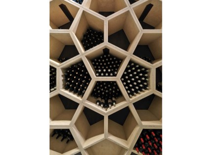 The so-called archive, a storage area for very special wines, was conceived as an entire wall of pentagonal wine shelves, which can be rearranged to a variety of patterns.